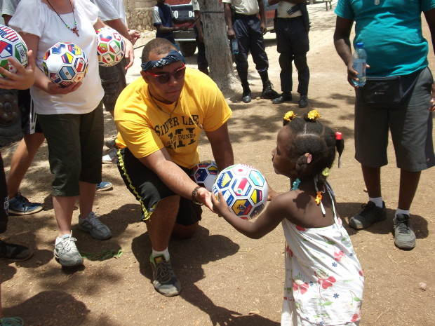 The cutest little girl ever receives a soccer ball from Haiti Team member Sean Kubit.