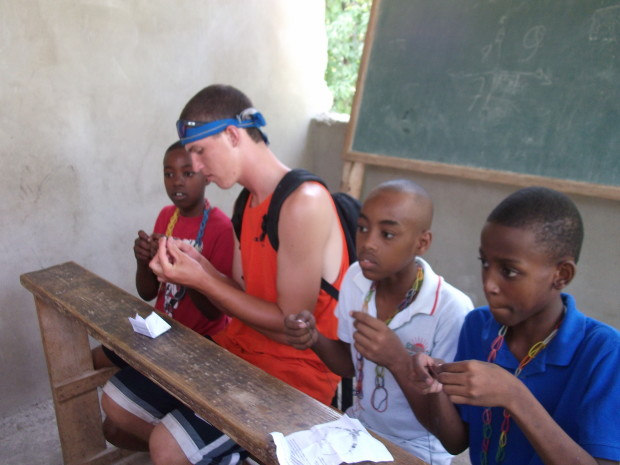 Lucas Serowoky makes gospel necklaces with the camp kids in Haiti.