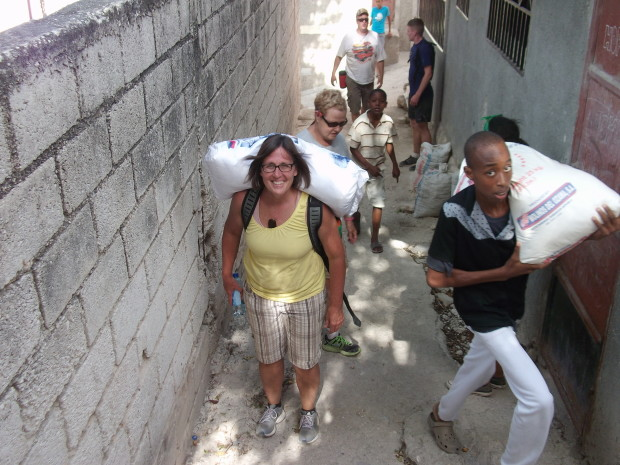 Several team members purchased rice for the orphanage. Denise Gosselin (in sunglasses) helps Teresa Serowoky balance a large bag of rice on her backpack as they walk back from the market.